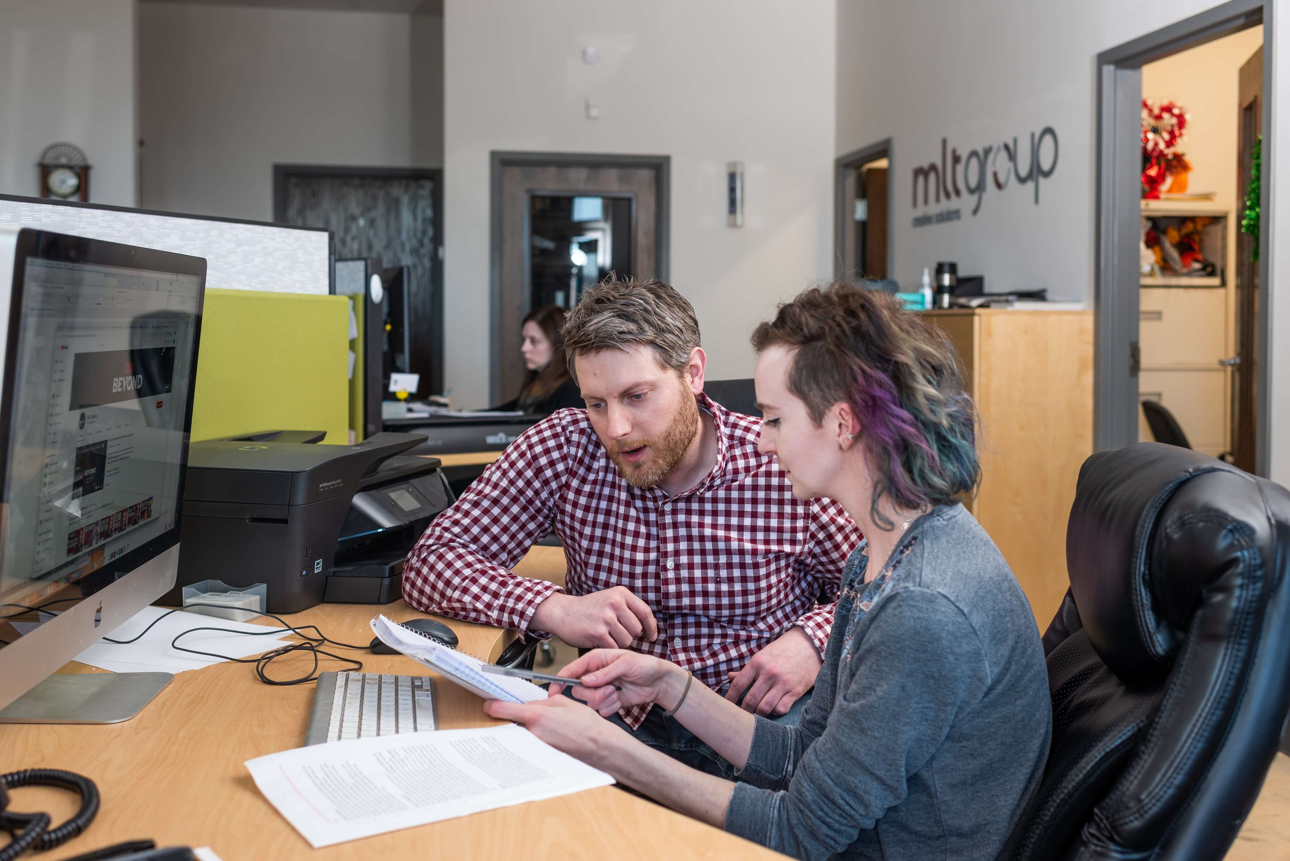 two people sitting at computer reviewing notes